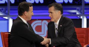 ... Rick Santorum (left) and Mitt Romney shake hands before the debate
